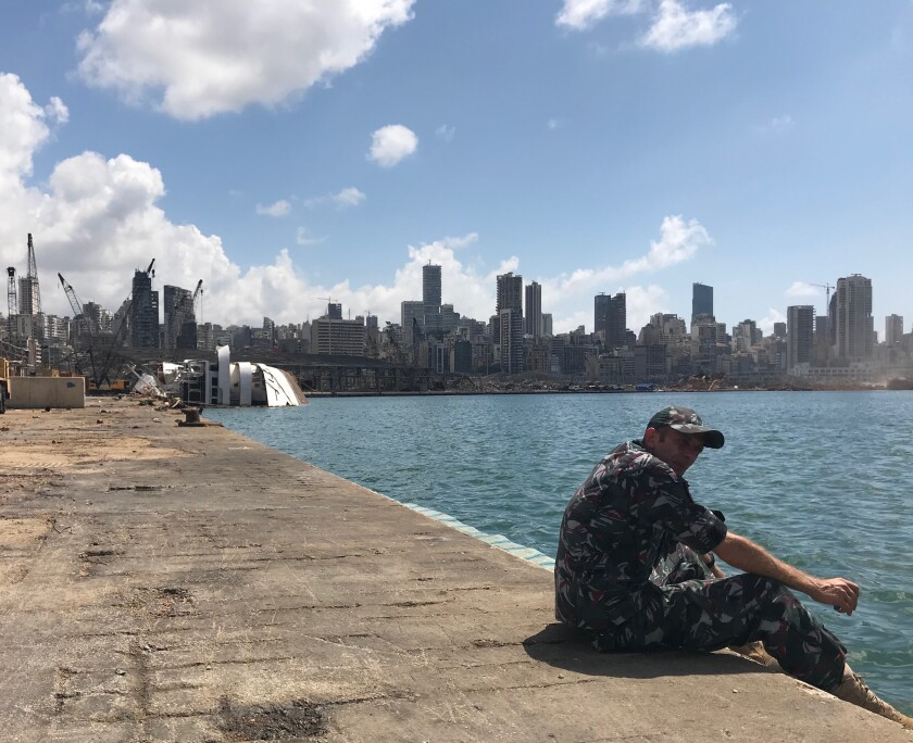 A security officer keeps watch in Beirut's port. The capsized Orient Queen cruise ship is seen in the background.