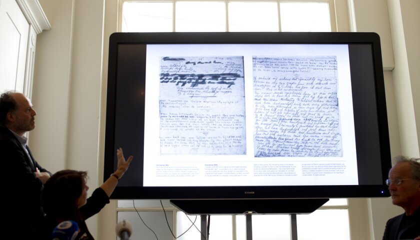 A video shows the text underneath two taped off pages from Anne Frank's diary during a press conference at The Anne Frank Foundation's office in Amsterdam, Netherlands, Tuesday, May 15, 2018. Left standing is the foundation's director Ronald Leopold.