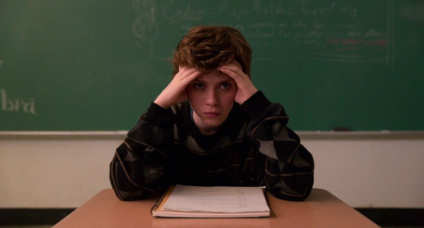 """Sophia Lillis sitting at a desk in front of a chalkboard in """"I Am Not Okay With This."""""""