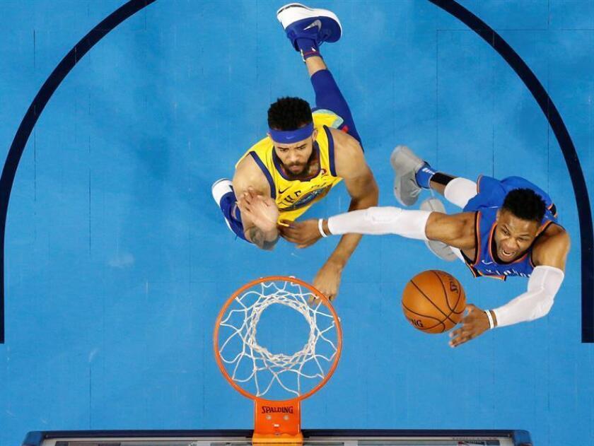 El jugador de los Golden State Warriors JaVale McGee (i) en acción ante Russell Westbrook (d) de los Oklahoma City Thunder, durante un partido de la NBA entre los Golden State Warriors y los Oklahoma City Thunder, en el Chesapeake Energy Arena de la Ciudad de Oklahoma (EE.UU.). EFE