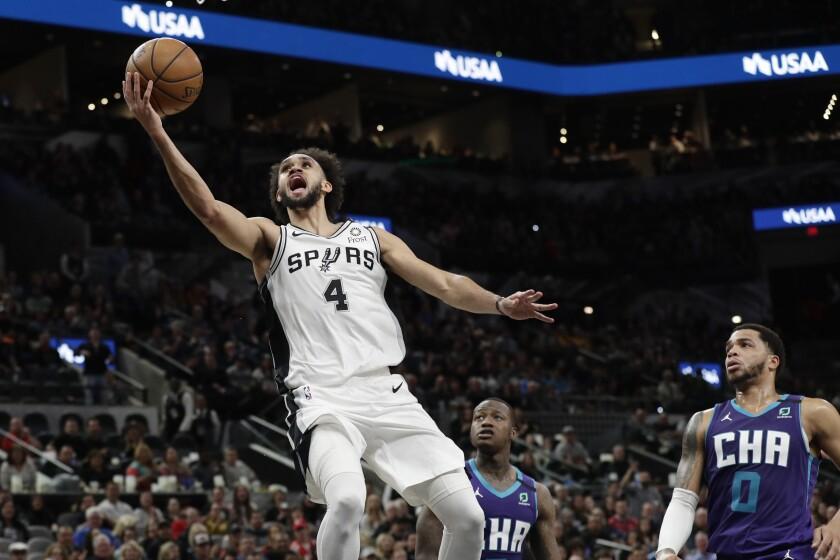 San Antonio Spurs guard Derrick White (4) scores past Charlotte Hornets forward Miles Bridges (0) during the second half of an NBA basketball game in San Antonio, Saturday, Feb. 1, 2020. (AP Photo/Eric Gay)