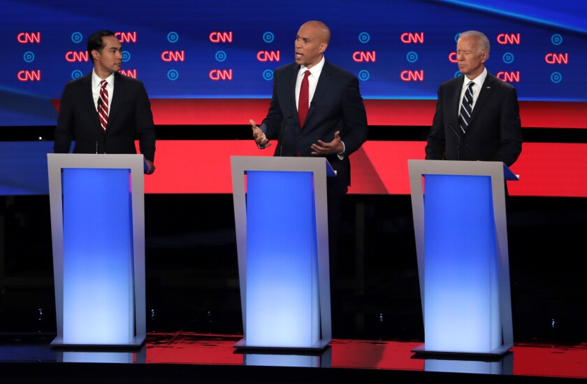 Sen. Cory Booker (D-N.J.) speaks while former Housing Secretary Julian Castro, left, and former Vice President Joe Biden listen during Wednesday night's Democratic presidential debate in Detroit.