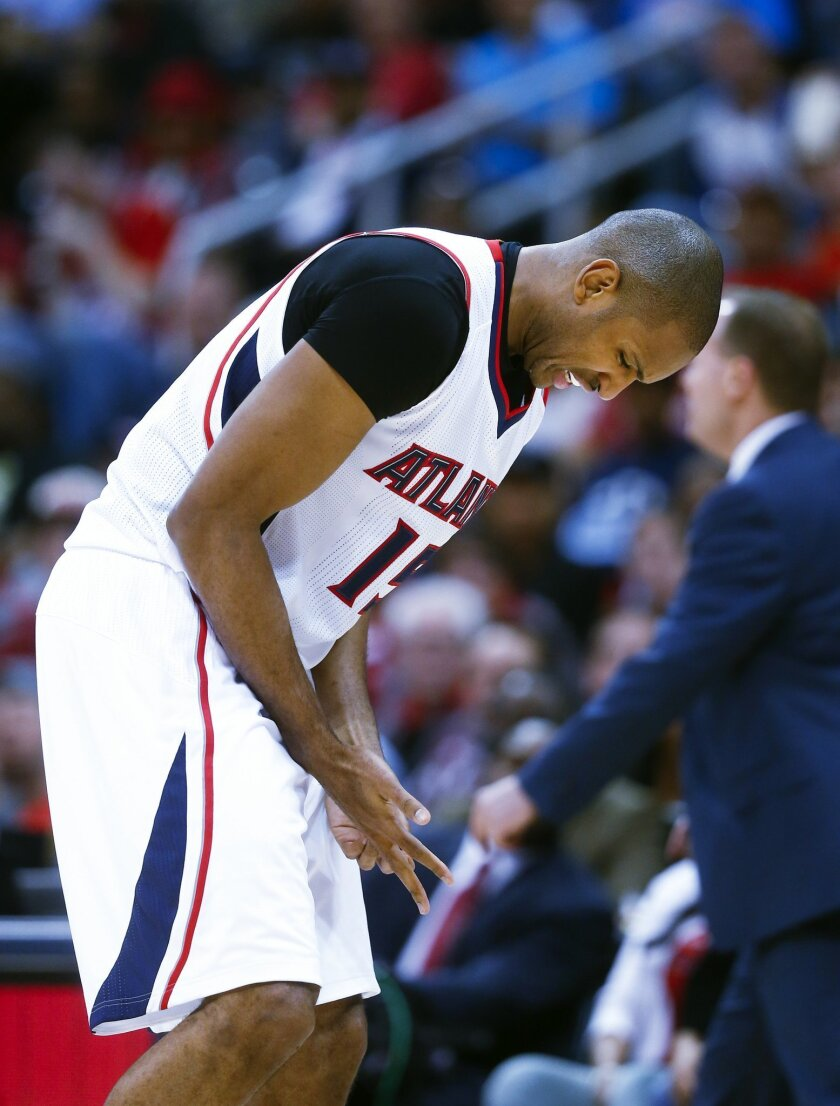 Atlanta Hawks center Al Horford (15) holds his finger as he walks off the court after being injured in the second half of an NBA playoff basketball game against the Brooklyn Nets, Sunday, April 19, 2015, in Atlanta. Atlanta won 99-92. (AP Photo/John Bazemore)