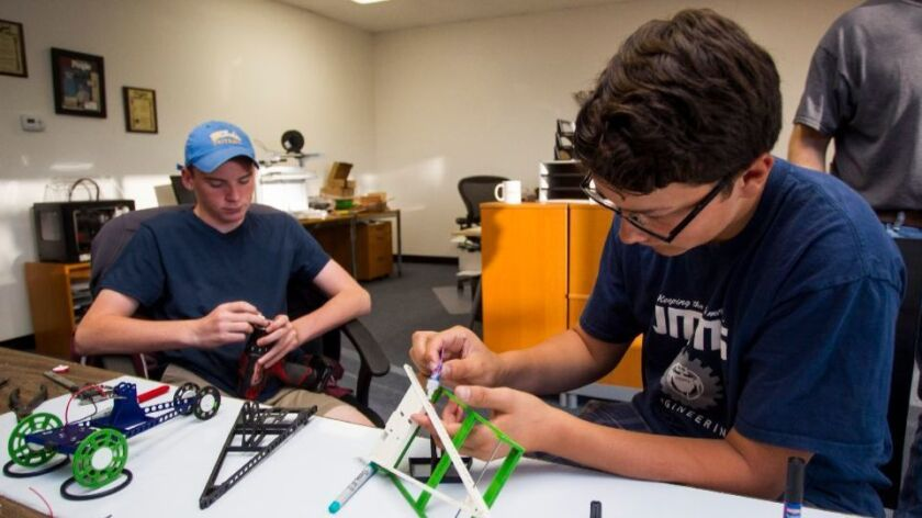 Hayden Loarie and Ramses Lara, eighth graders at Joan MacQueen Middle School, work on a solar-powere
