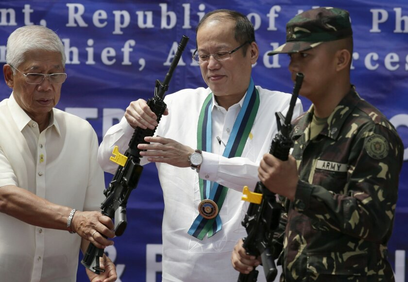 Philippine President Benigno Aquino III, center, hands brand new assault rifles to Filipino soldiers in a ceremonial distribution Thursday, Aug. 14, 2014 at the General Headquarters of the Armed Forces at suburban Quezon city, northeast of Manila, Philippines. More than 50,000 M4 assault rifles are to be delivered within this year as part of the Armed Forces of the Philippines modernization program. At left is defense chief Voltaire Gazmin. (AP Photo/Bullit Marquez)