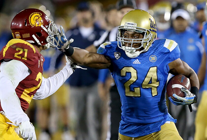 USC safety Su'a Cravens (21) fends off a stiff-arm move by Bruins running back Paul Perkins to make a tackle after a reception during last season's rivalry game.