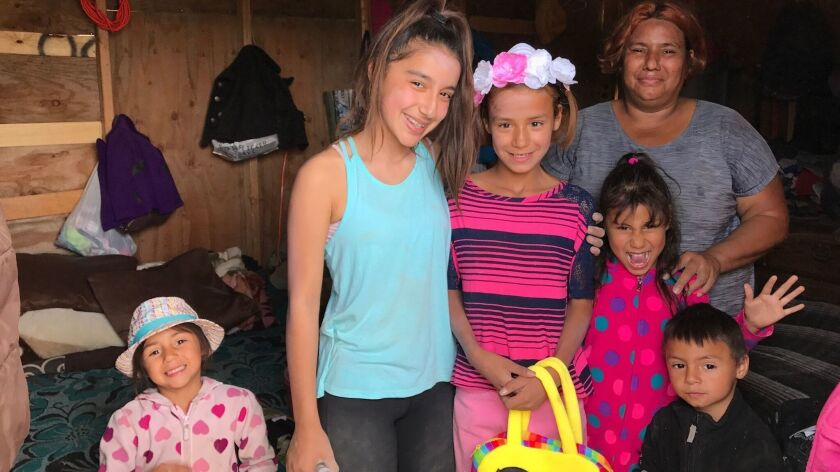 Daniella Benitez, 13, in the turquoise top, raised $16,000 to build and furnish a home in Tijuana for this mother and her four kids. They lived in this shack before Benitez and Build a Miracle volunteers constructed their hew house.