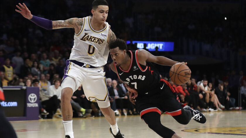 The Toronto Raptors' Kyle Lowry dribbles next to Lakers' Kyle Kuzma during the second half on Nov. 4. The Lakers suffered a lopsided 121-107 loss to the Raptors.