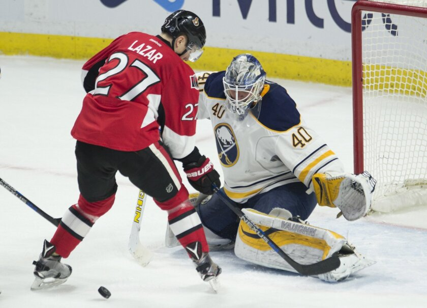 Ottawa Senators' right wing Curtis Lazar (27) loses sight of the puck in front of Buffalo Sabres' goalie Robin Lehner during the second period of an NHL hockey game, Tuesday, Feb. 16, 2016 in Ottawa, Ontario.  (Adrian Wyld/The Canadian Press via AP) MANDATORY CREDIT