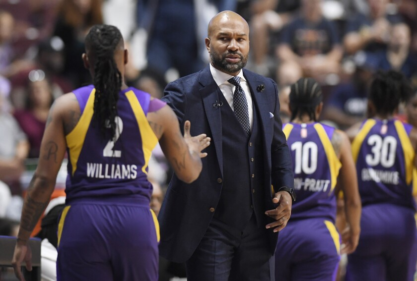Sparks coach Derek Fisher greets guard Riquna Williams as she exits the court during the first half of a WNBA playoff game against the Sun on Sept. 17, 2019, in Uncasville, Conn.