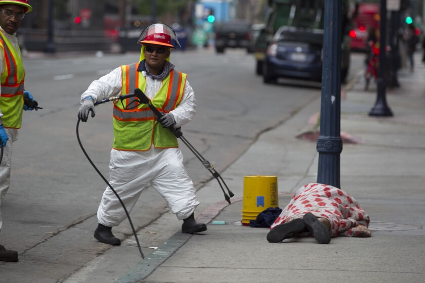 Spraying the sidewalk on First Avenue. The sleeper, right, was awakened and moved long enough so his patch of concrete could be cleaned, too.