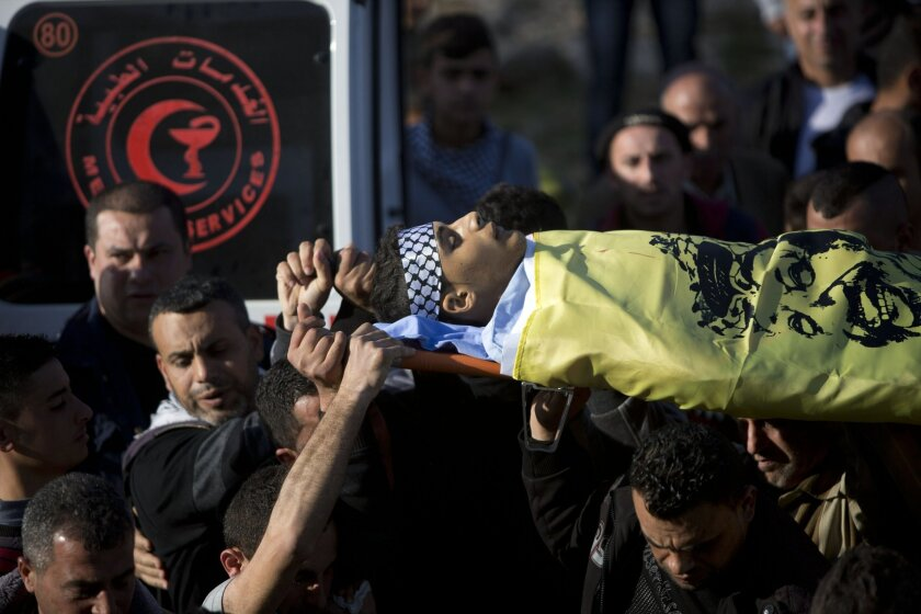 Palestinian mourners carry the body of  Nihad Waked, 15, who was shot dead by Israeli troops with Fouad Waked, 15, during their funeral in the village of Aeraqh near the West Bank city of Jenin, Sunday, Feb. 14, 2016. The Israeli army said the two teenagers were throwing rocks at passing vehicles n