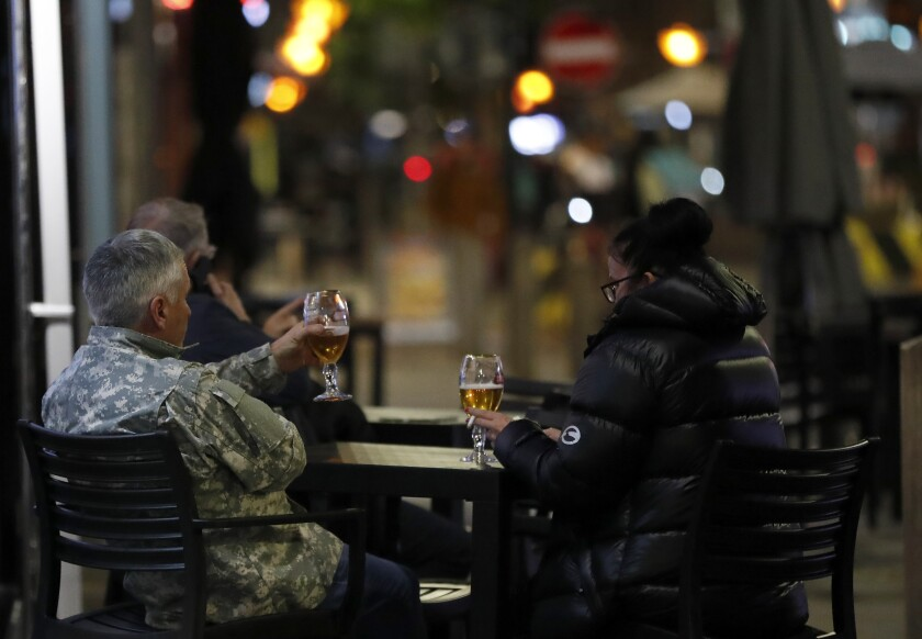 People drink a beer outside a restaurant in Liverpool, England, Wednesday, Oct. 14, 2020. As the first area in England slapped with strict new restrictions to curb the resurgent coronavirus that have shuttered pubs and imperiled thousands of jobs, Liverpool again feels it's being punished by policies made in Britain's capital, 180 miles (290 kilometers) to the south. (AP Photo/Frank Augstein)