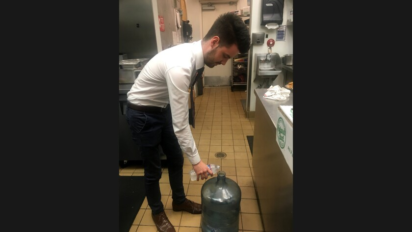 Conor Black, 20, a management intern at the Avalon Grille, pours a diner's leftover bottled water into a 5-gallon container that will be used later to mop floors and nourish plants.