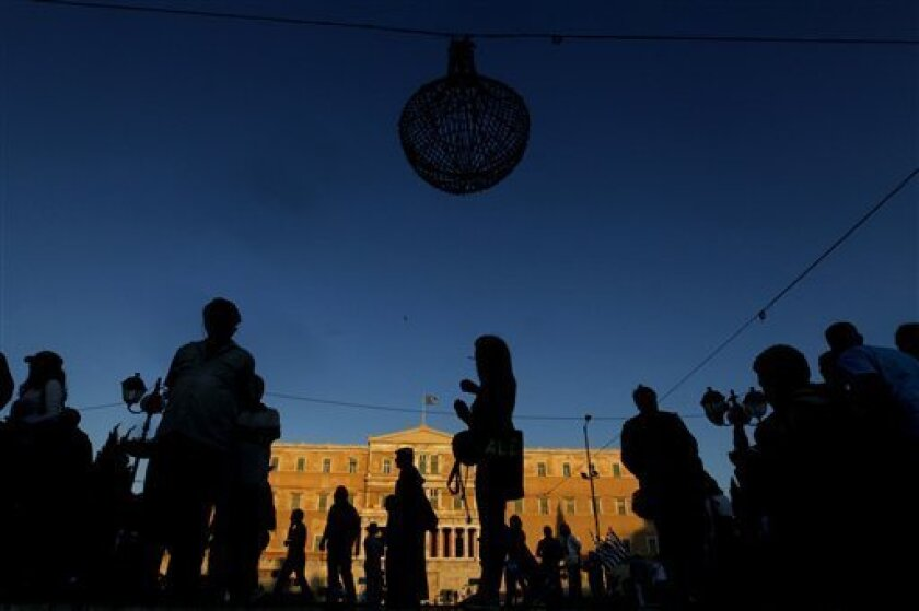 People walks in front of Greek parliament in central Athens, on Thursday, Sept. 29, 2011. Greeks have been protesting the latest round of austerity measures, which the government has announced in an effort to secure the next installment of its bailout loans. (AP Photo/Petros Giannakouris)