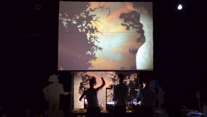 """Manual Cinema presents its """"live films"""" using overhead projectors, shadow puppets, silhouetted actors and live music. Company members are visible below the screen, so the audience gets to see the process as well as the product."""