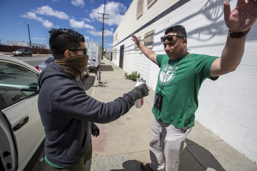 In coronavirus fight, workers in ski masks are holding L.A.'s social safety net together
