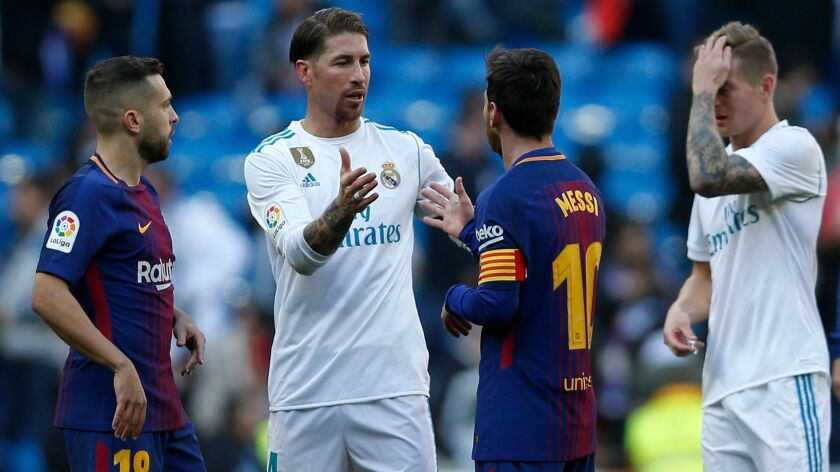 Real Madrid's Sergio Ramos, center left, shakes hands with Barcelona's Lionel Messi at the end of th