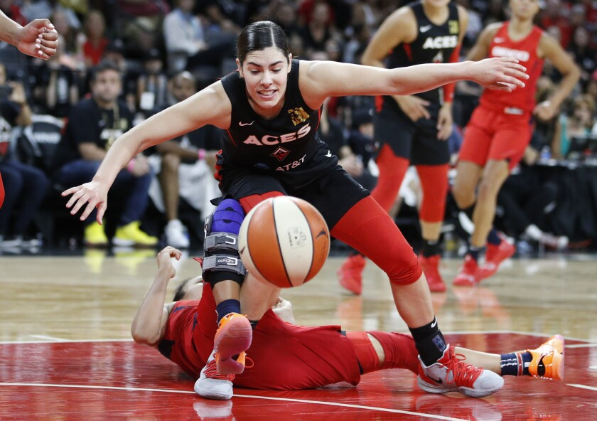 Las Vegas Aces' Kelsey Plum, top, falls into Washington Mystics' Kristi Toliver during the second half in Game 3 in the semifinals of the WNBA playoffs, Sunday, Sept. 22, 2019, in Las Vegas. (AP Photo/John Locher)