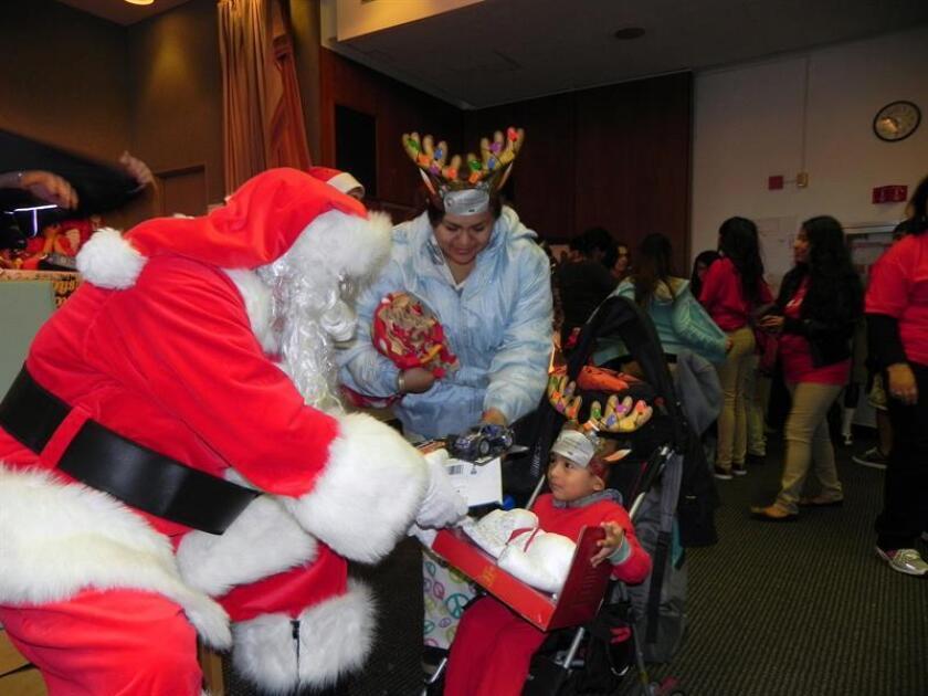 Santa Claus entrega un juguete a un niño. EFE/Archivo