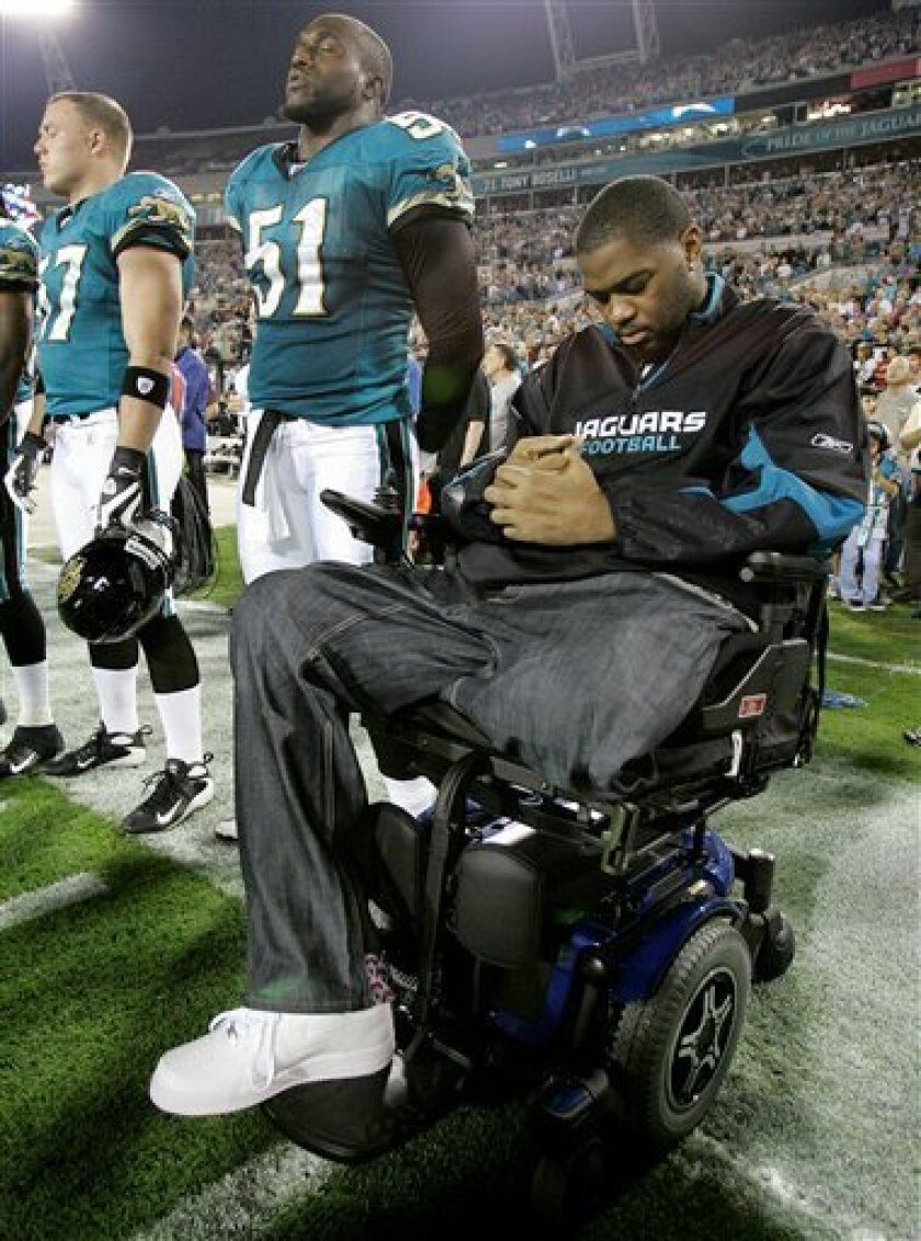 Jacksonville Jaguars offensive lineman Richard Collier joins his teammates on the sidelines for the national anthem before the Jaguars' NFL football game against the Indianapolis Colts, Thursday, Dec. 18, 2008, in Jacksonville, Fla. Collier was paralyzed from the waist down following a shooting in early September. (AP Photo/Phil Coale)
