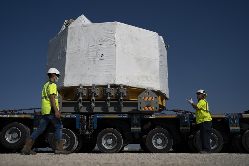 Workers receive a central solenoid magnet  for the International Thermonuclear Experimental Reactor project.