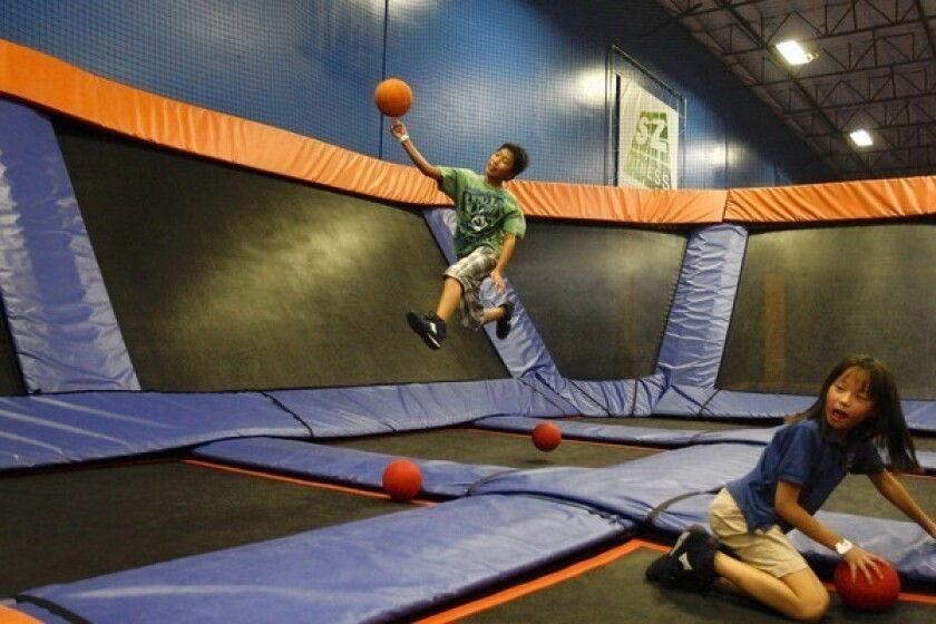 Micah Kim, 10, of Anaheim jumps high off a trampoline to throw a dodge ball as Lauren Lee, 8, also of Anaheim, grabs a ball at the Sky Zone trampoline park in Anaheim. Jerry Raymond, CEO of Sky High Sports and a founding member of the International Assn. of Trampoline Parks, estimates there are just over 100 facilities in the United States, and expects that number to grow.