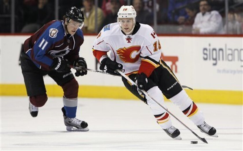 Calgary Flames center Matt Stajan, front, picks up loose puck as Colorado Avalanche left wing Jamie McGinn trails during the second period of an NHL hockey game in Denver on Thursday, Feb. 28, 2013. (AP Photo/David Zalubowski)
