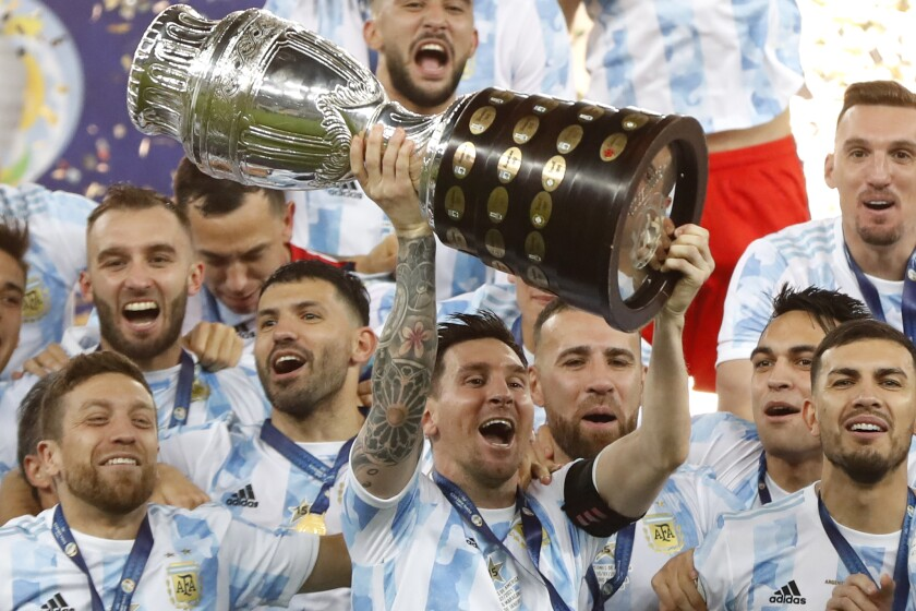 Argentina's Lionel Messi holds the trophy as he celebrates with the team after beating 1-0 Brazil in the Copa America final soccer match at the Maracana stadium in Rio de Janeiro, Brazil, Saturday, July 10, 2021. (AP Photo/Andre Penner)