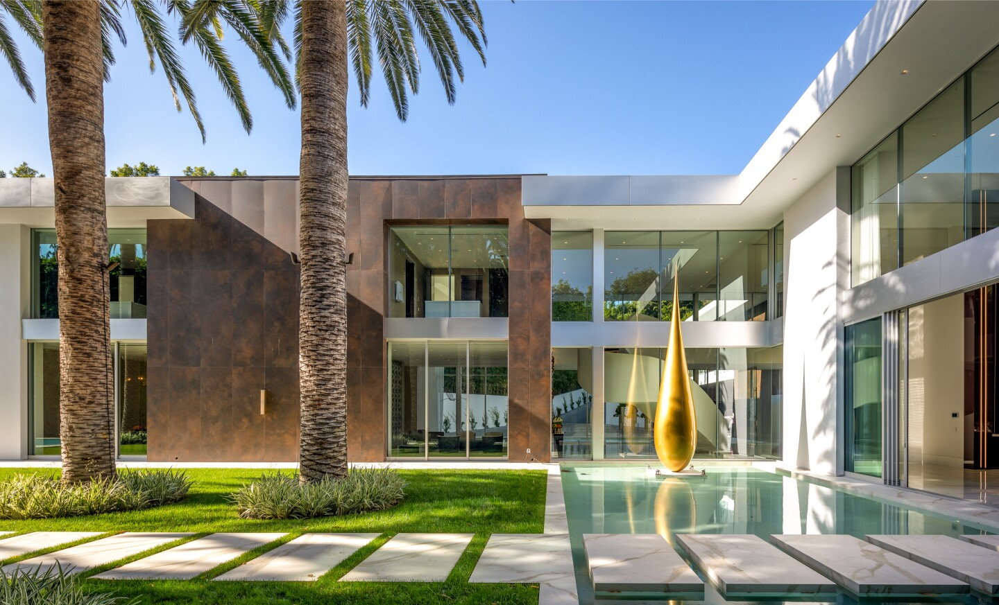 Spanning two acres, the gated property holds a nearly 30,000-square-foot mansion, a 160-foot pool and a 30-foot water wall.