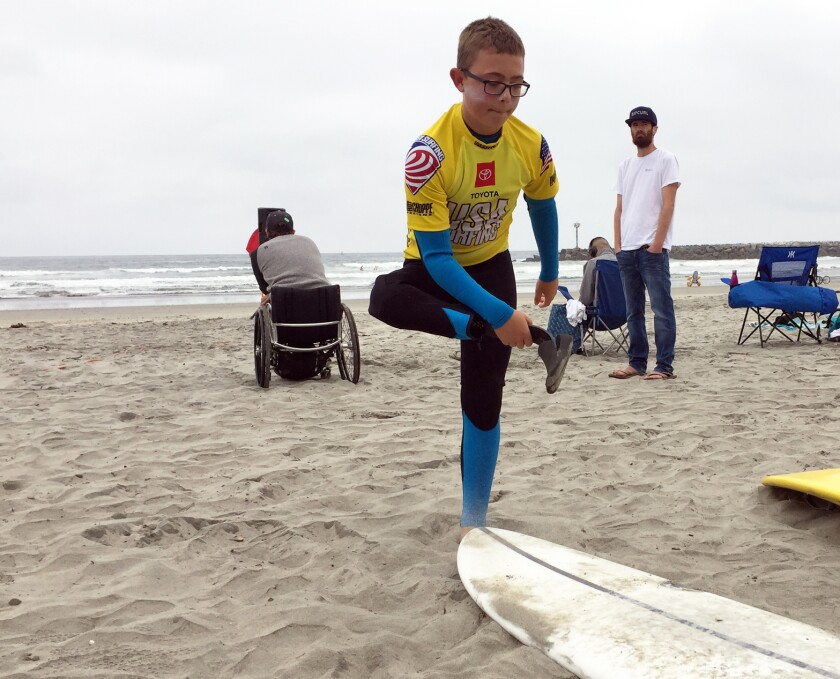 William Thompson, 12, of Little Rock, Calif., adjusts his prosthetic leg at USA Surfing's 2019 Adaptive Surfing Championship Thursday at Oceanside Harbor's North Jetty beach.