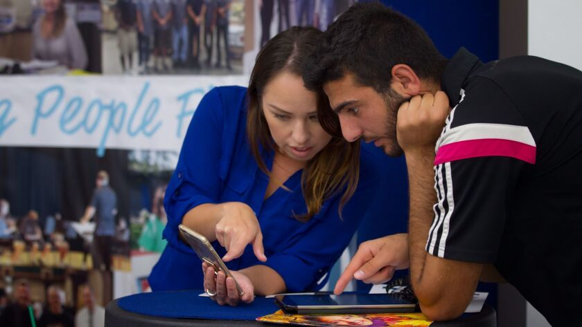 Raizen Elia (cq) who arrived in the U.S. back in 2010 from Iraq gets assistance from Maritza Diaz fr