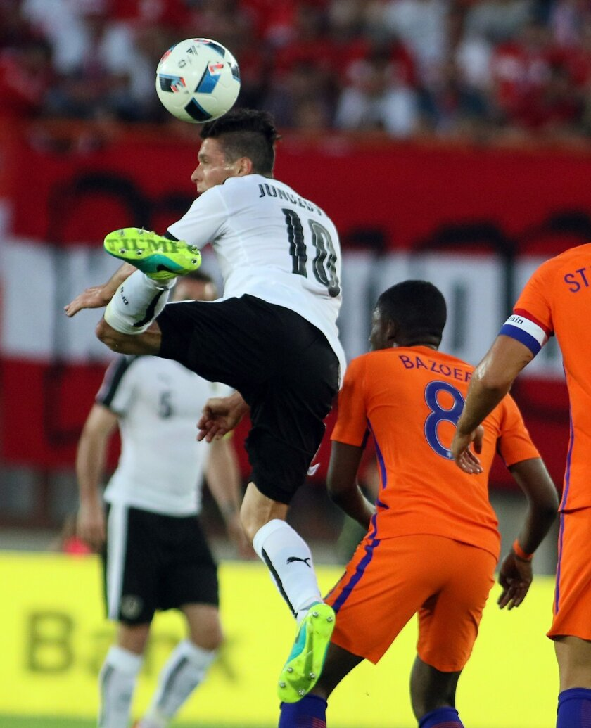 Zlatko Junuzovic of Austria battles for the ball with Netherlands' Riecedly Bazoer, from left, during an international friendly soccer match between Austria and The Netherlands in Vienna, Austria, Saturday, June 4, 2016. (AP Photo/Ronald Zak)