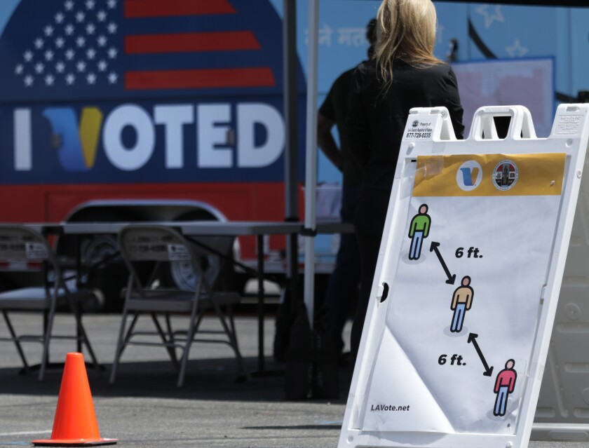 A sign encourages people to keep six feet apart at a polling place in Santa Clarita in May