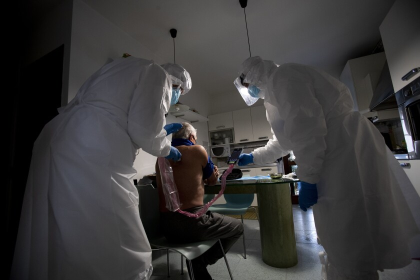 Doctor Luigi Cavanna, left, visits COVID-19 patient Arnaldo Michelotti in his home in Gossolengo, near Piacenza, Italy, Wednesday, Dec. 2, 2020. (AP Photo/Antonio Calanni)