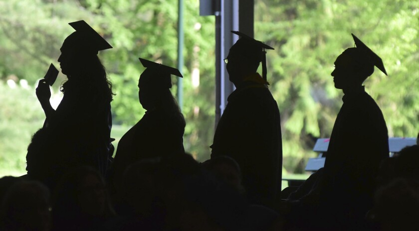 FILE - In this Friday, June 1, 2018, file photo, graduates are silhouetted against the green landscape as they line up to receive their diplomas at Berkshire Community College's commencement exercises at the Shed at Tanglewood in Lenox, Mass. Some lenders advertise their products as a way to pay for college, but these aren't technically student loans. For unsuspecting students, that could lead to unnecessarily high costs and a lack of consumer protection. (Gillian Jones/The Berkshire Eagle via AP, File)