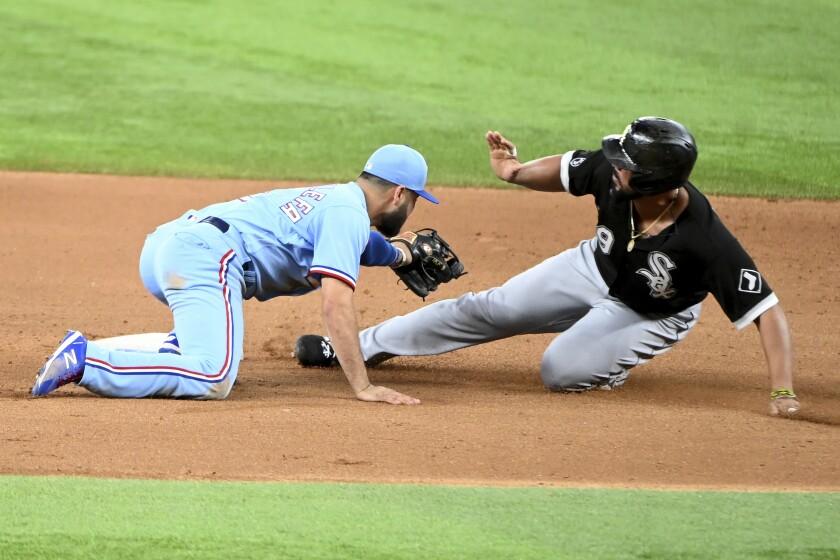 José Abreu, derecha, de Medias Blancas de Chicago, se barre en segunda base y evita que Isiah Kiner-Falefa, izquierda, de Rangers de Texas, lo retire en la séptima entrada del juego de beisbol en Arlington, Texas, el domingo 19 de septiembre de 2021. (AP Foto/Matt Strasen)