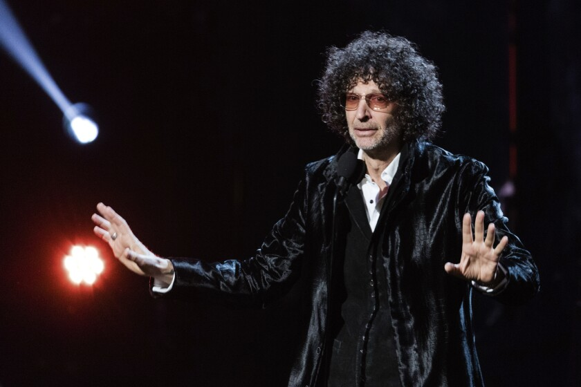 A man with voluminous, curly hair in a shiny black suit speaks onstage