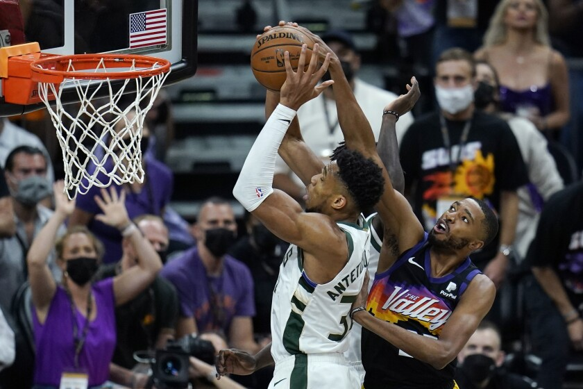Milwaukee Bucks forward Giannis Antetokounmpo, left, gabs a rebound as Phoenix Suns forward Mikal Bridges, right, arrives late during the first half of Game 1 of basketball's NBA Finals, Tuesday, July 6, 2021, in Phoenix. (AP Photo/Ross D. Franklin)