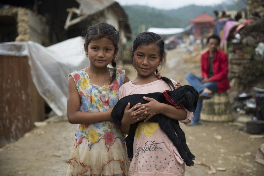 Two girls -- Dipika, left, and Susila -- hold a family goat in Pahade Thapa Gaon, an agricultural village outside Katmandu where the Humane Society International has deployed emergency animal welfare aid.
