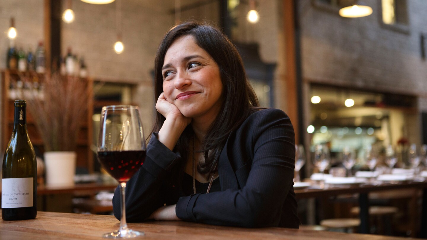Sommelier Maria Garcia sits for a portrait with a glass of wine at Republique restaurant.
