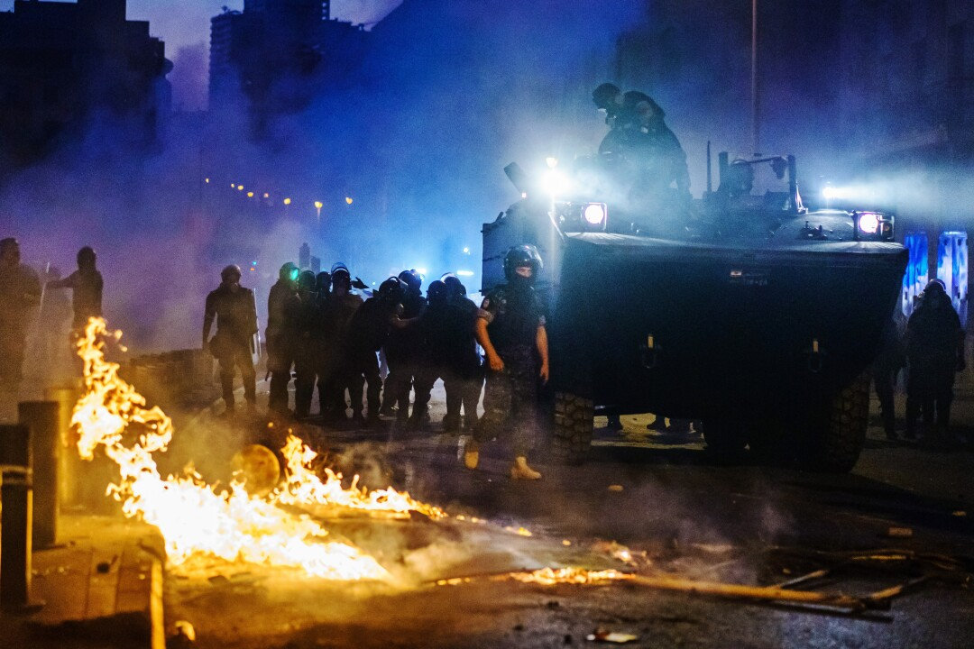 A police vehicle and officers in riot gear move through purplish haze and past flames leaping on the street.