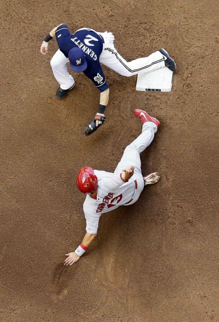 Milwaukee Brewers second baseman Scooter Gennett tags out St. Louis Cardinals' Matt Carpenter at second as he is caught stealing during the fifth inning of a baseball game Sunday, Sept. 7, 2014, in Milwaukee. (AP Photo/Morry Gash)