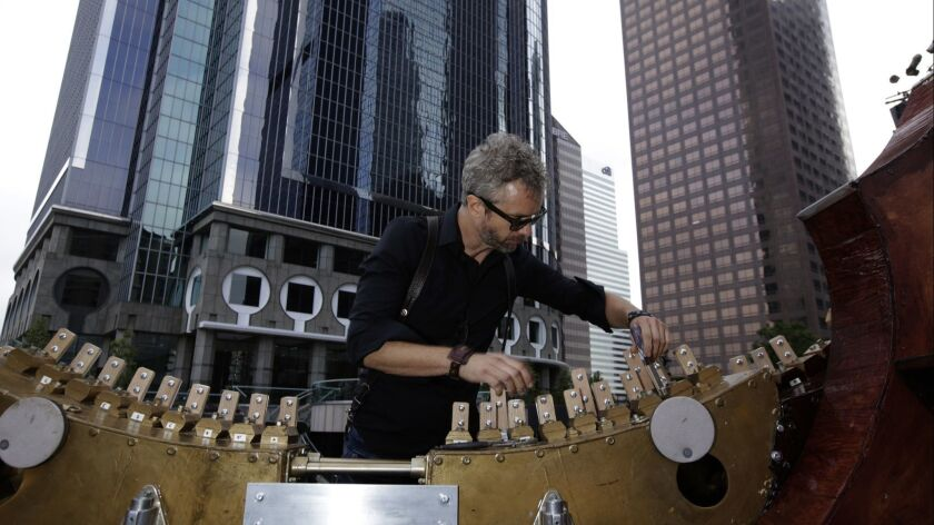William Close prepares to string his Earth Harp, which is the largest playable stringed instrument in the world. This photo was taken before a performance in downtown Los Angeles in May 2017, when he connected the harp's strings to the skyscraper behind him.