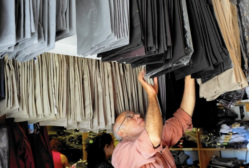 Sigifredo Lopez, who sells school uniforms out of his shop in Pacoima, fears that he will be run out of business if L.A. legalizes street vending.