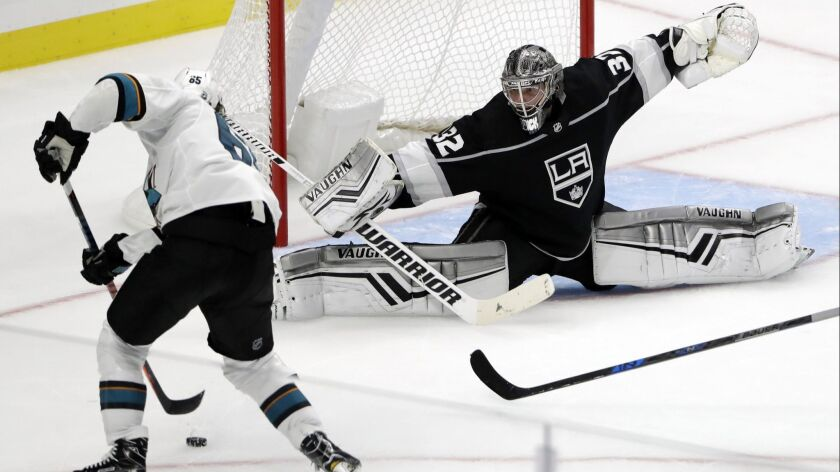 Los Angeles Kings goaltender Jonathan Quick defends on San Jose Sharks' Erik Karlsson during the thi