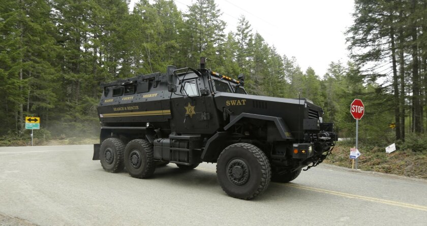 A Mason County Sheriff Dept. SWAT vehicle drives a few miles from the scene of a fatal shooting Friday, Feb. 26, 2016, near Belfair, Wash. (AP Photo/Ted S. Warren)