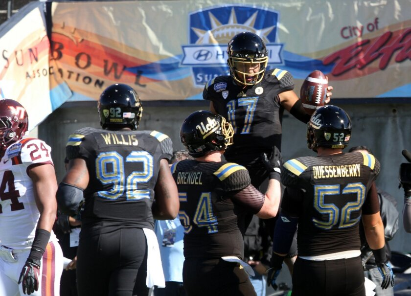 UCLA quarterback Brett Hundley (17) celebrates with teammates after a first quarter touchdown against Virginia Tech in the Sun Bowl NCAA college football game Tuesday Dec. 31, 2013, in El Paso, Texas. (AP Photo/Victor Calzada)