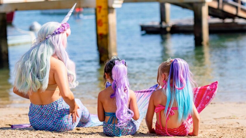 A mermaid from Once Upon An Island entertains two kiddie mermaids on the Balboa Island beach near the business.