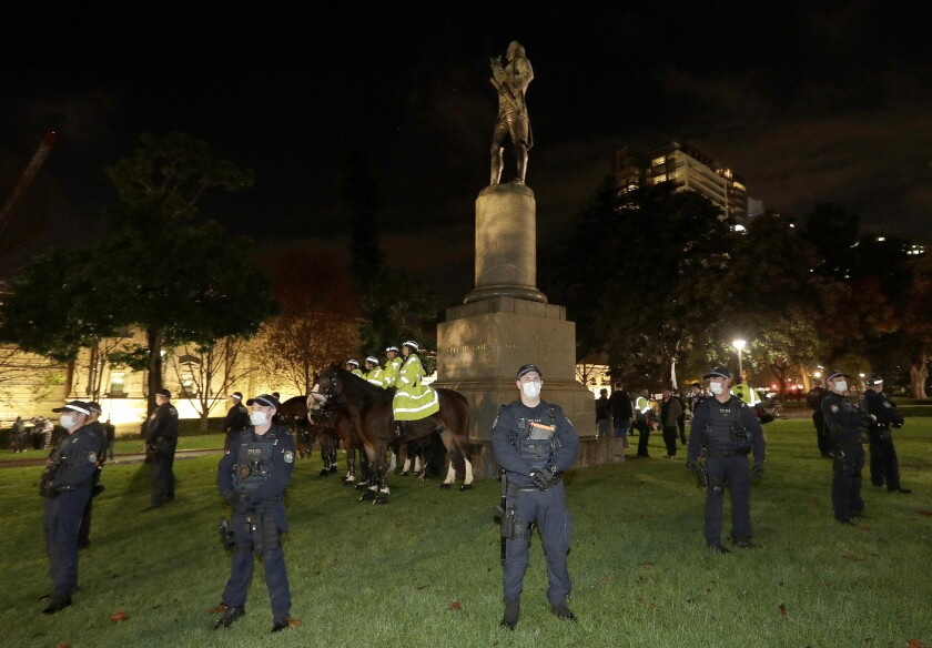 FILE - In this June 12, 2020, file photo, police guard a statue of British explorer James Cook as protesters gather in Sydney, to support U.S. protests over the death of George Floyd. An Australian state government leader said on Monday, June 15, 2020 she was considering tougher laws to protect monuments after two statues of British explorer James Cook were vandalized in Sydney. (AP Photo/Rick Rycroft, File)